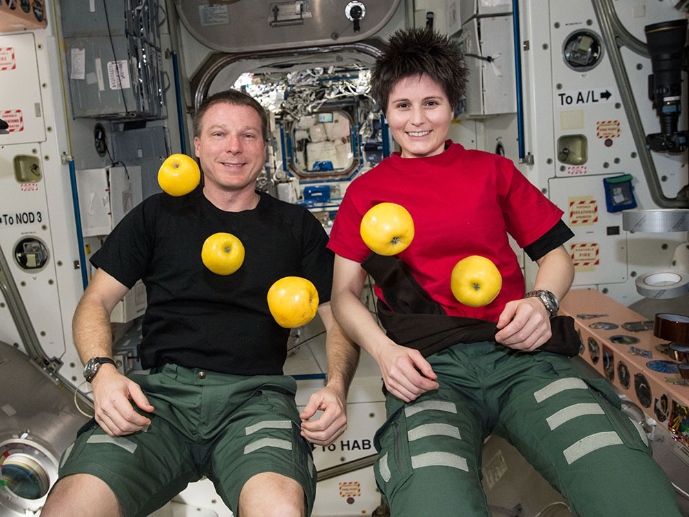 Terry Virst and Samantha Cristoforetti share some fruit aboard the International Space Station.